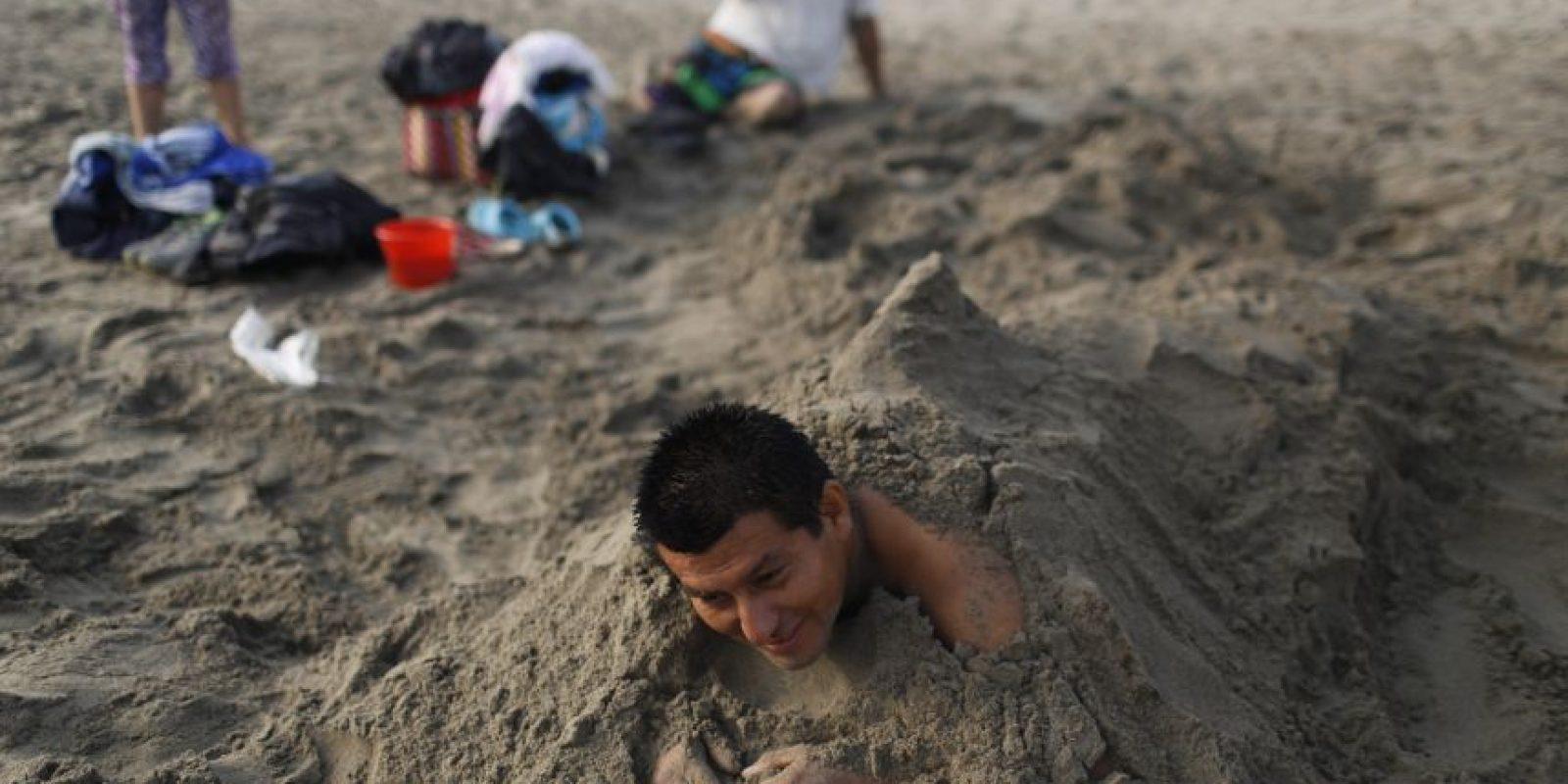 """En esta imagen, tomada el 25 de abril de 2015, Víctor Villanueva descansa en la arena de la playa Pescadores durante una sesión de """"arenoterapia"""" en la costa del océano Pacífico en Lima, Perú. Villanueva es uno de los muchos que practican talasoterapia en la costa limeña en busca de alivio para dolencias que los médicos no han podido curar. Foto:AP/ Rodrigo Abd"""
