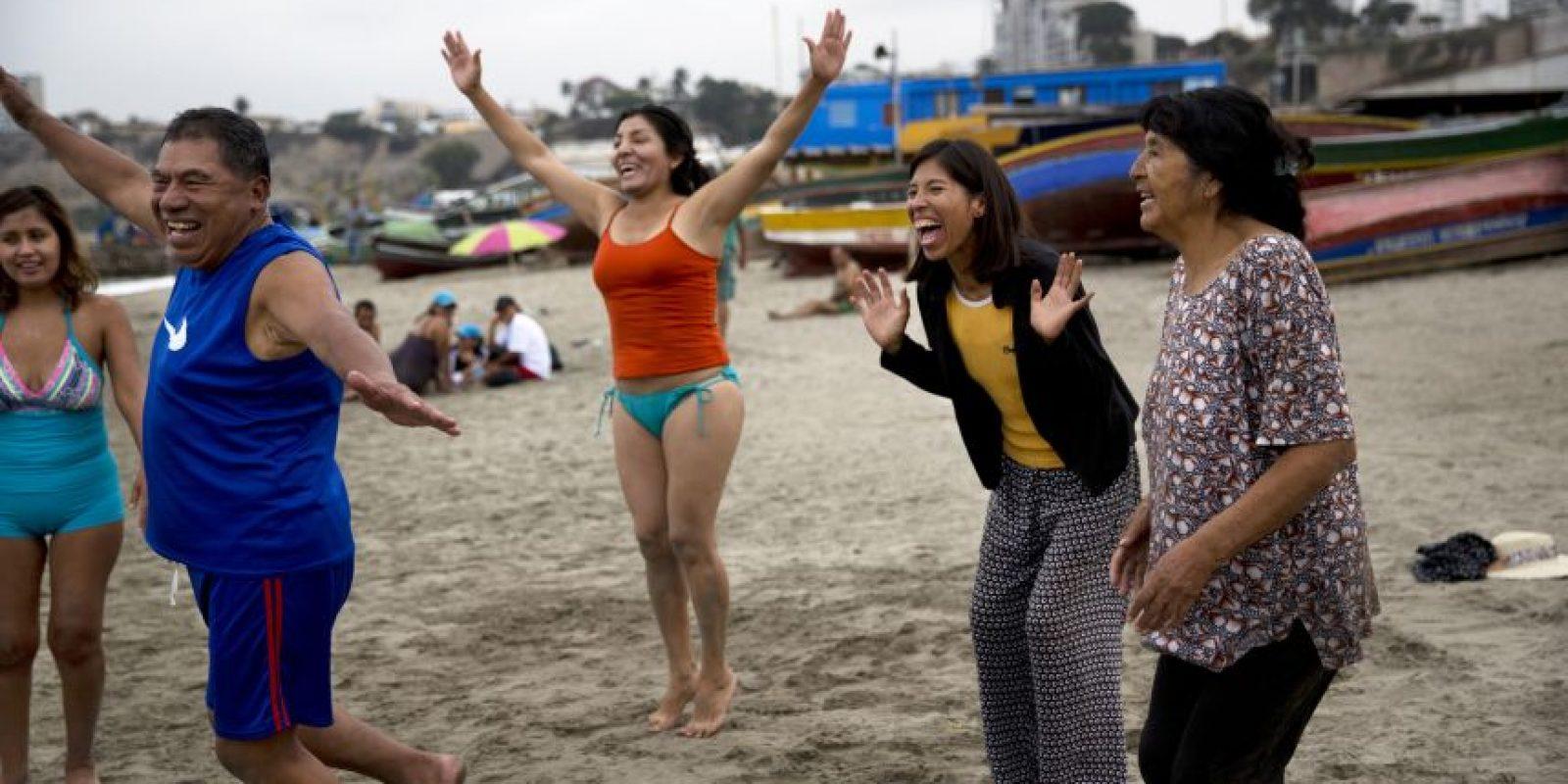 """En esta imagen, tomada el 8 de mayo de 2015, un grupo de personas sonríe durante una sesión de risoterapia en la playa Pescadores de Lima, Perú. El promotor de terapias naturales José Cusquisiban organiza grupos de terapia y hace que sus pacientes corran descalzos por la arena. """"Luego hacemos un círculo armonioso de oración, después cantamos, practicamos la risoterapia, nos abrazamos y finalmente entramos al mar y le enseñamos a nadar a los que no saben"""", agregó. Foto:AP/ Rodrigo Abd"""