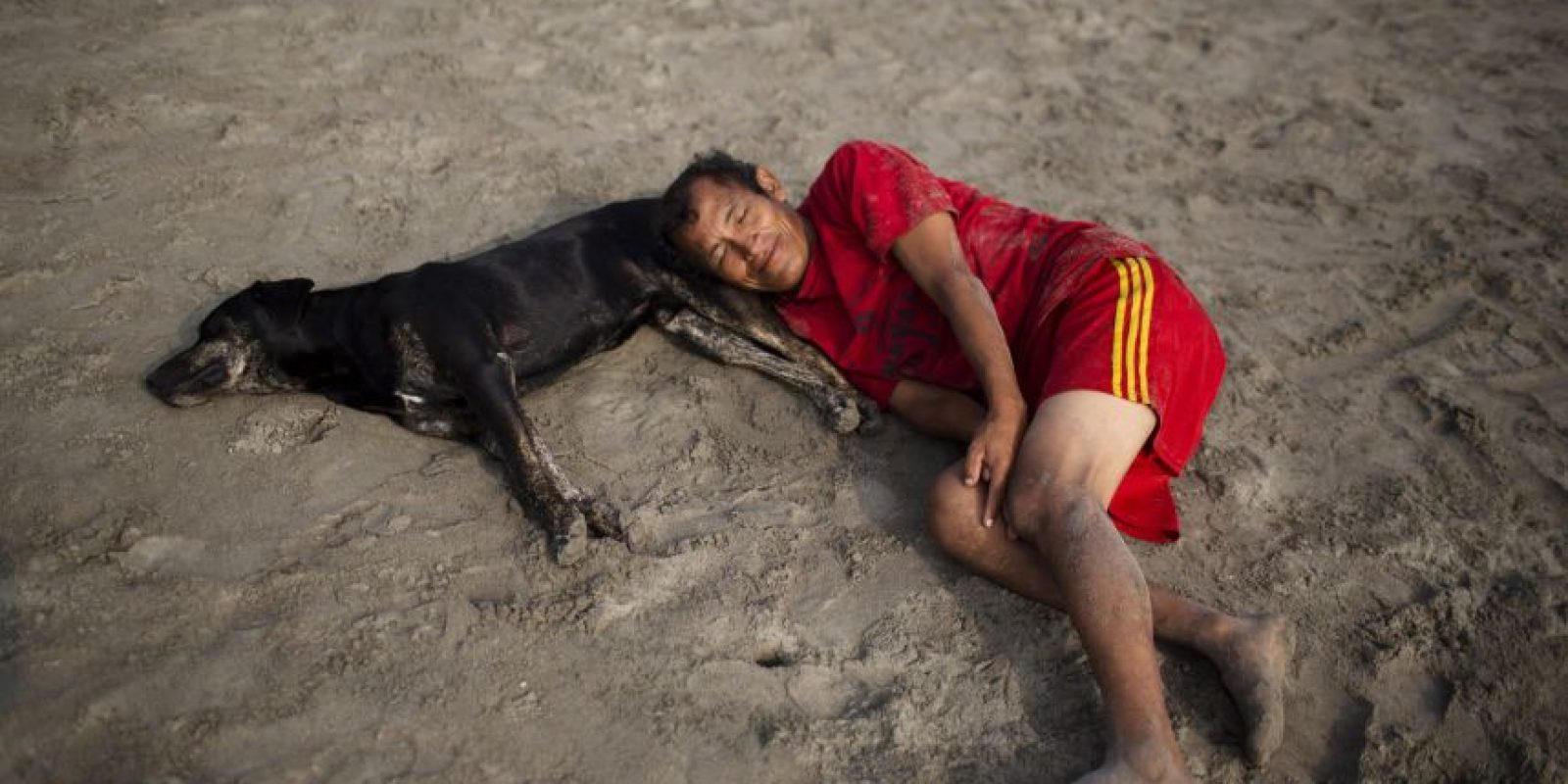 En esta foto, tomada el 25 de abril de 2015, un hombre y un perro descansan sobre la arena de la playa Pescadores antes de un baño terapéutico en sus aguas, en Lima, Perú. En la costa de Lima, la gente busca alivio para las dolencias que los médicos no han sido capaces de tratar. Foto:AP/ Rodrigo Abd