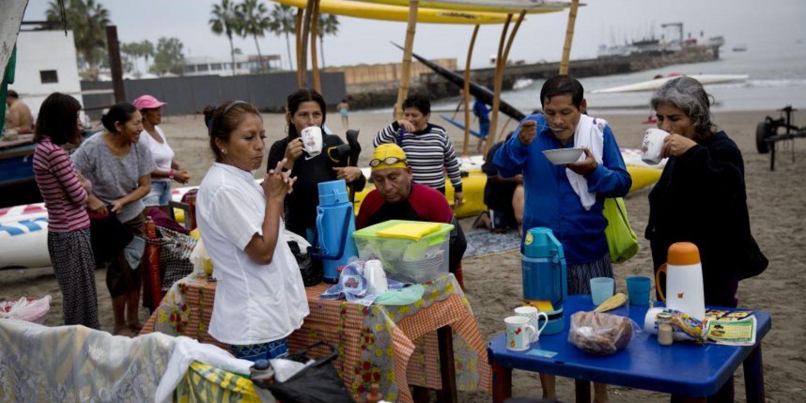 """En esta imagen, tomada el 15 de mayo de 2015, bañistas desayunan en la playa Pescadores frente al océano Pacífico en Lima, Perú. Los bañistas compran sus alimentos a un vendedor de """"comida sana"""" tras una sesión de baño terapéutico. Foto:AP/ Rodrigo Abd"""