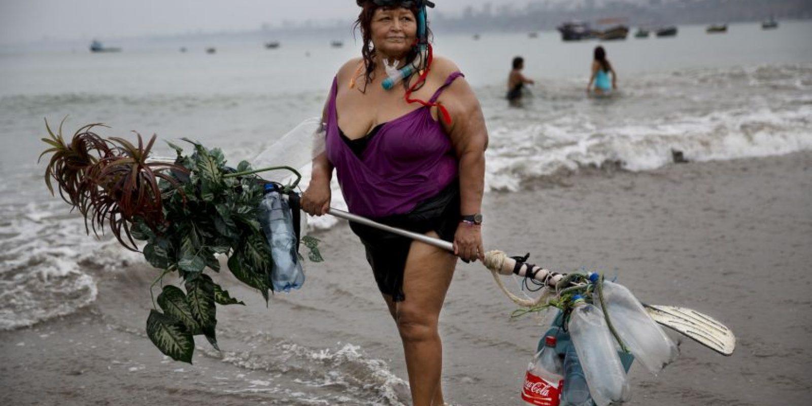 En esta imagen, tomada el 7 de mayo de 2015, Graciela Meneses posa para una foto en la playa Pescadores sosteniendo un flotador fabricado por ella, decorado con plantas falsas de plástico, tras nadar en aguas del océano Pacífico en Lima, Perú. Graciela, de 67 años, dijo que perdió 39 kgs (85 libras) ejercitándose en el mar. Foto:AP/ Rodrigo Abd
