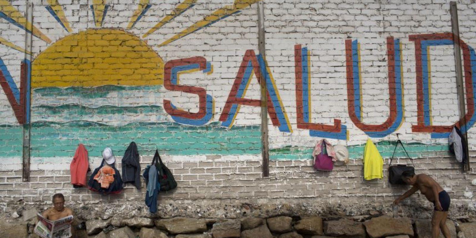 """En esta foto, tomada el 25 de abril de 2015, un hombre lee el periódico junto a una pared con un sol y la palabra """"Salud"""" pintados en la playa Pescadores, donde acuden los bañistas para baños terapéuticos, en Lima, Perú. Algunos se abrazan en grupo, saltando, riendo y corriendo junto a la orilla. Otros se bañan en silencio en el mar tranquilo y gris. Foto:AP/ Rodrigo Abd"""