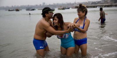"""En esta imagen, tomada el 8 de mayo de 2015, dos amigos ayudan a Gisela Sánchez, quien sufre artritis reumatoide, a meterse en el agua de la playa de los Pescadores, en Lima, Perú. """"La arena calma la inflamación en mis articulaciones y el mar me da tranquilidad"""", dijo Sánchez, quien viajó hasta allí desde Patapo, una localidad a los pies de los Andes a unos 700 kms (1.690 millas) al norte de Lima. Sánchez, de 25 años, dice que no puede caminar por sí misma en los últimos cuatro años, y espera que el mar la ayude a volver a andar. Foto:AP/ Rodrigo Abd"""