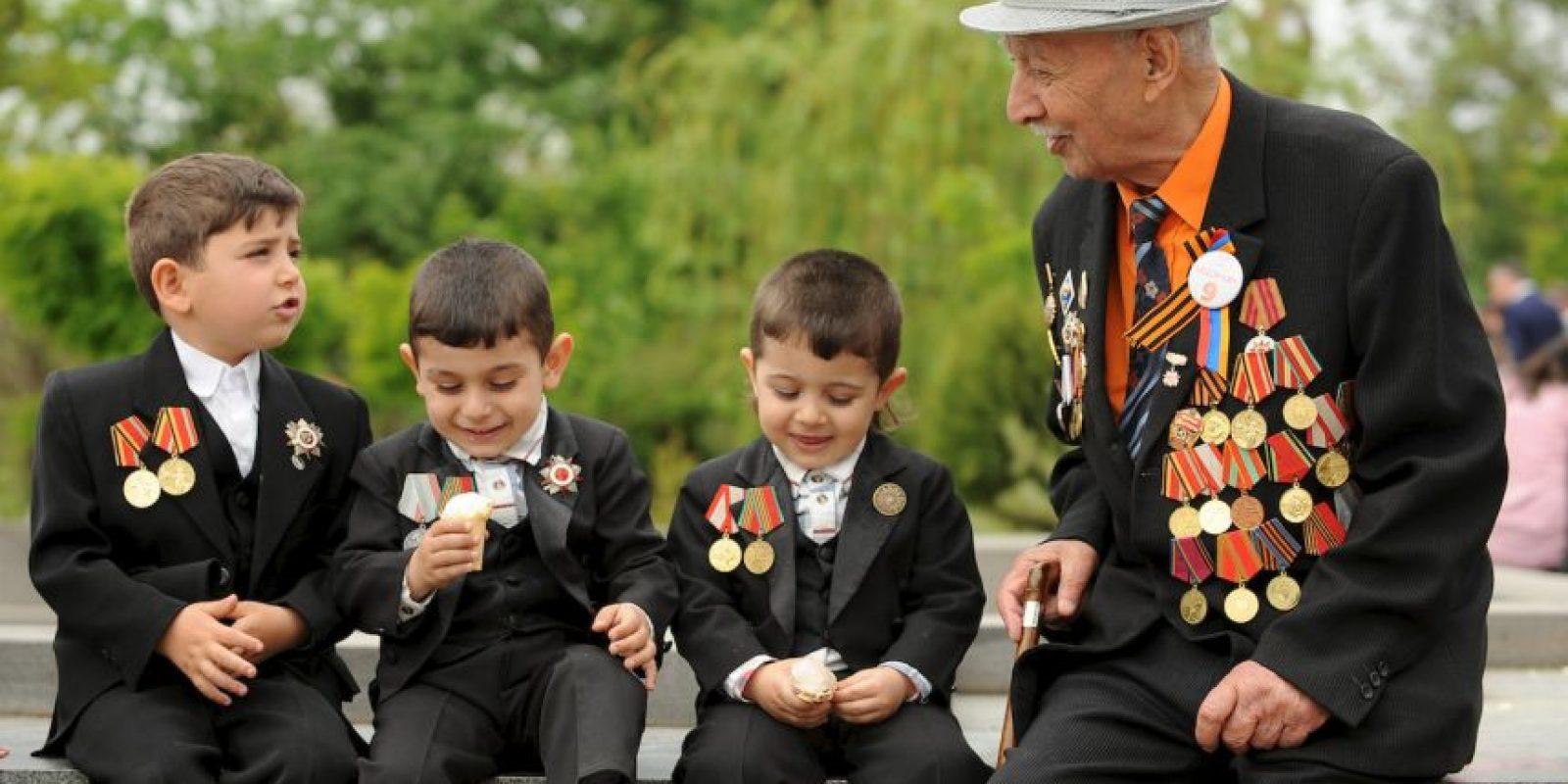 Un veterano comparte con niños en la conmemoración del Día de la Victoria en Armenia. Foto:AFP