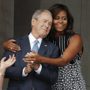 First lady Michelle Obama hugs former President George W. Bush during the dedication ceremony for the Smithsonian Museum of African American History and Culture on the National Mall in Washington, Saturday, Sept. 24, 2016. (AP Photo/Pablo Martinez Monsivais)