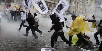 Manifestantes corren por una calle inundada para escapar del gas lacrimógeno lanzado por la policía después de que una marcha del Día del Trabajo desatara algunos choques en el centro de Bogotá, Colombia  Foto:AP