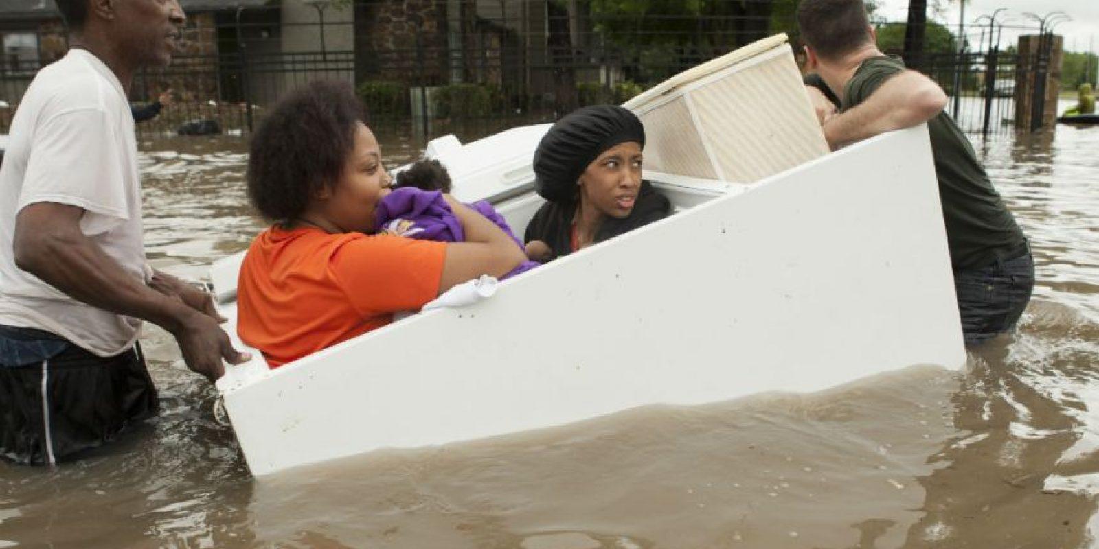 Personas de un complejo de apartamentos se retiran del lugar, algunas arriba de un refrigerador convertido en canoa, en The Woodlands, Texas. Foto:AP
