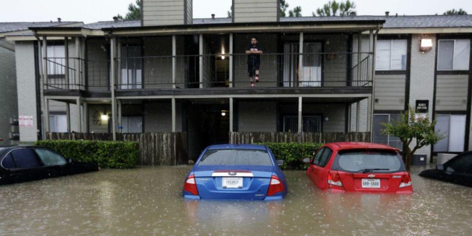Un residente observa desde el segundo piso la inundación en el edificio de apartamentos en donde vive. Foto:AP