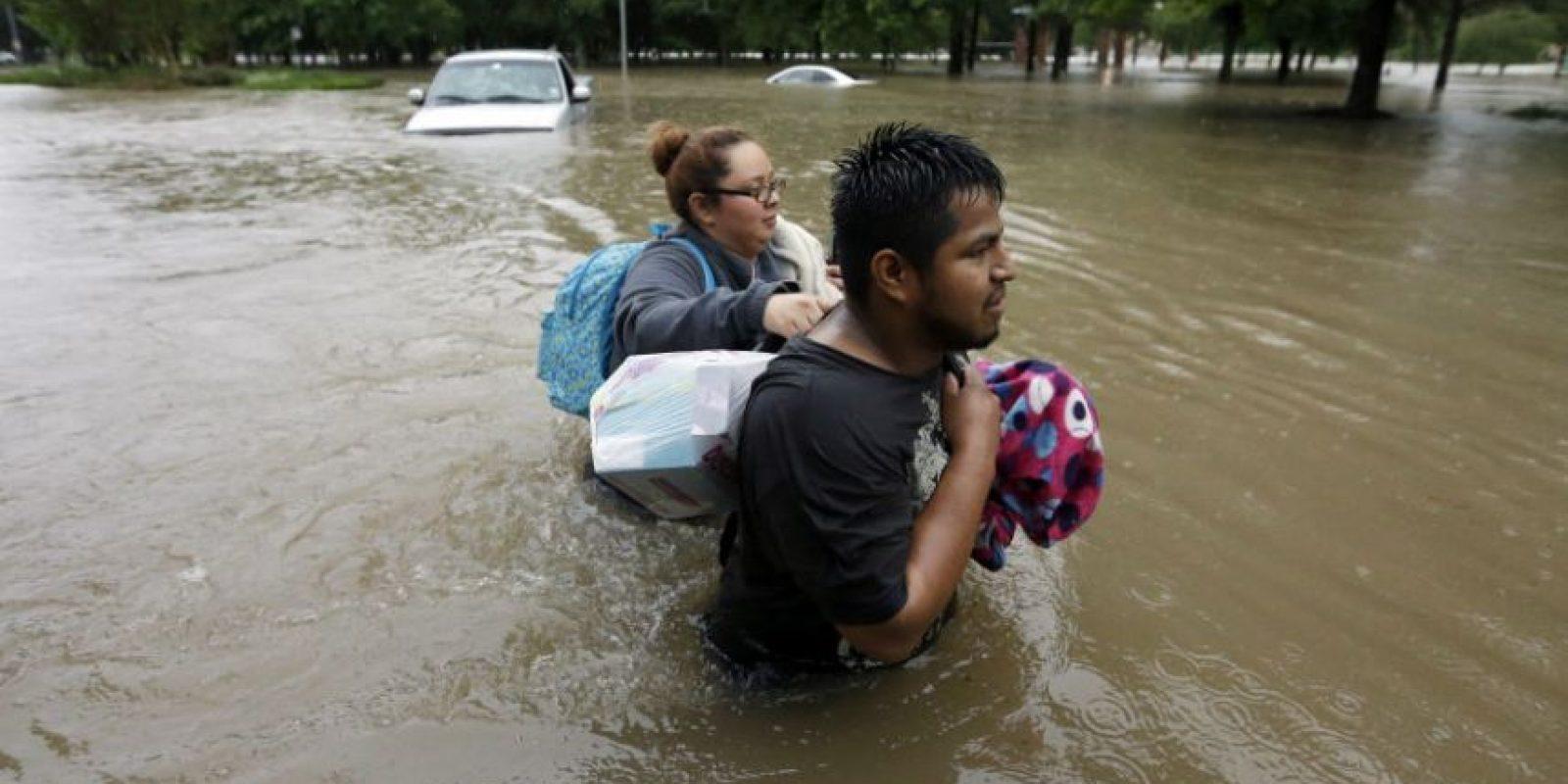 Margarita Uribe y su esposo, Juan Juárez, caminan entre el agua mientras salen del edificio de apartamentos inundado en donde viven. Foto:AP