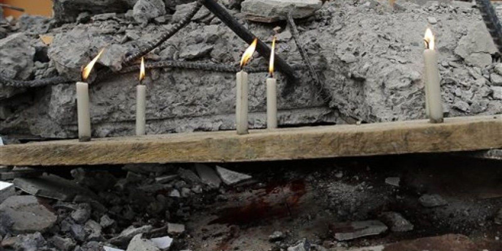 """Esta imagen, tomada el 18 de abril de 2016, muestra varias velas encendidas sobre una tabla, en memoria de los fallecidos en un terremoto de magnitud 7,8, en La Chorrera, Ecuador. La energía liberada por el sismo de Ecuador fue """"probablemente unas 20 veces mayor"""" que la generada por uno de magnitud 7,0 registrado antes el 16 de abril en Japón, explicó un profesor de geociencia de la Open University de Londres. (Foto AP/Dolores Ochoa) Foto:AP"""