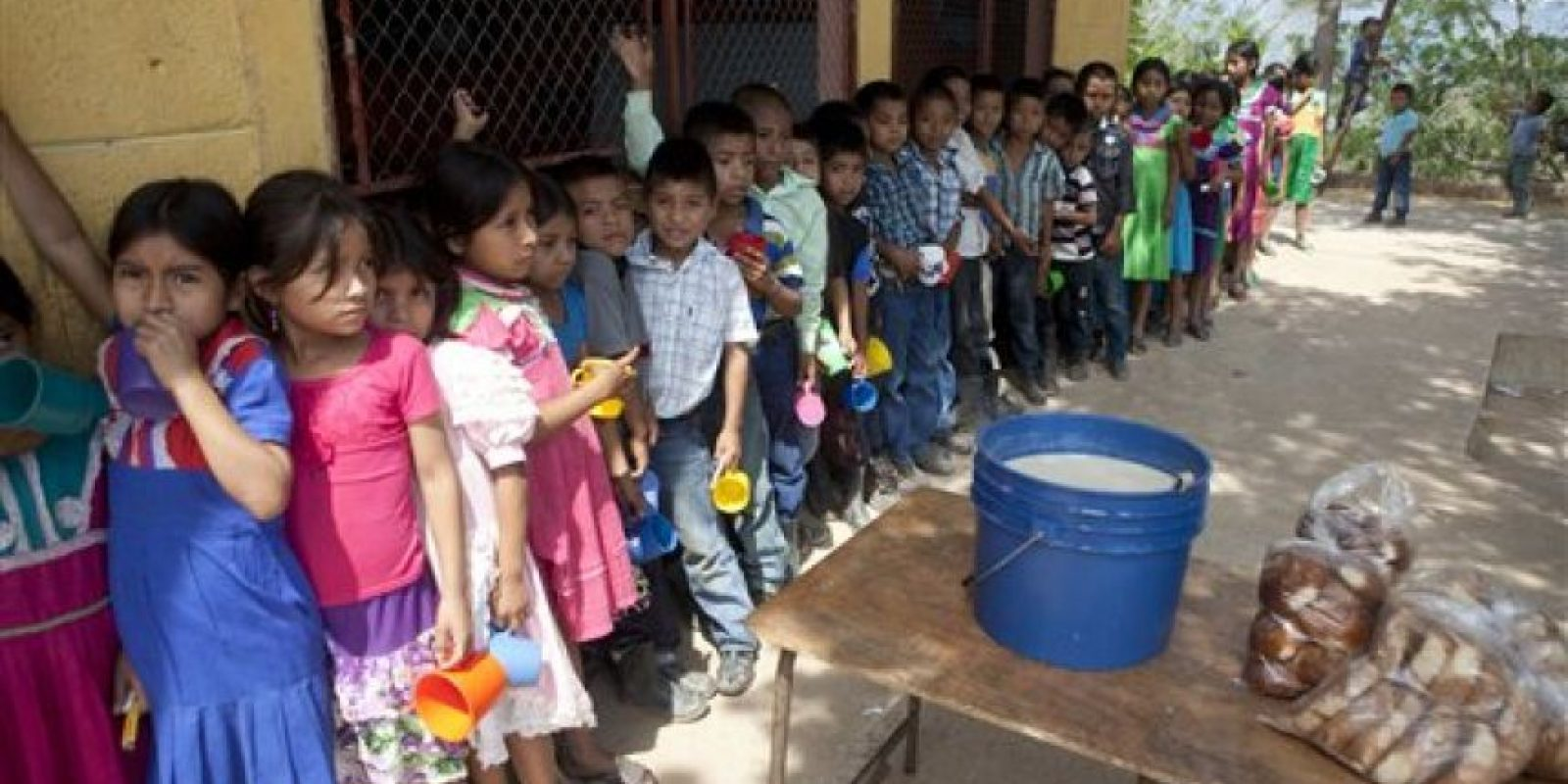 Estudiantes esperan que les llenen su taza con atole y les entreguen un pedazo de pan antes de iniciar con su jornada escolar en Guatemala. Foto:AP/ Archivo