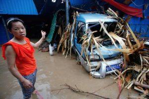 Una mujer señala un vehículo destrozado por las intensas lluvias en las sureñas provincias chinas. Foto:Getty Images/ Archivo