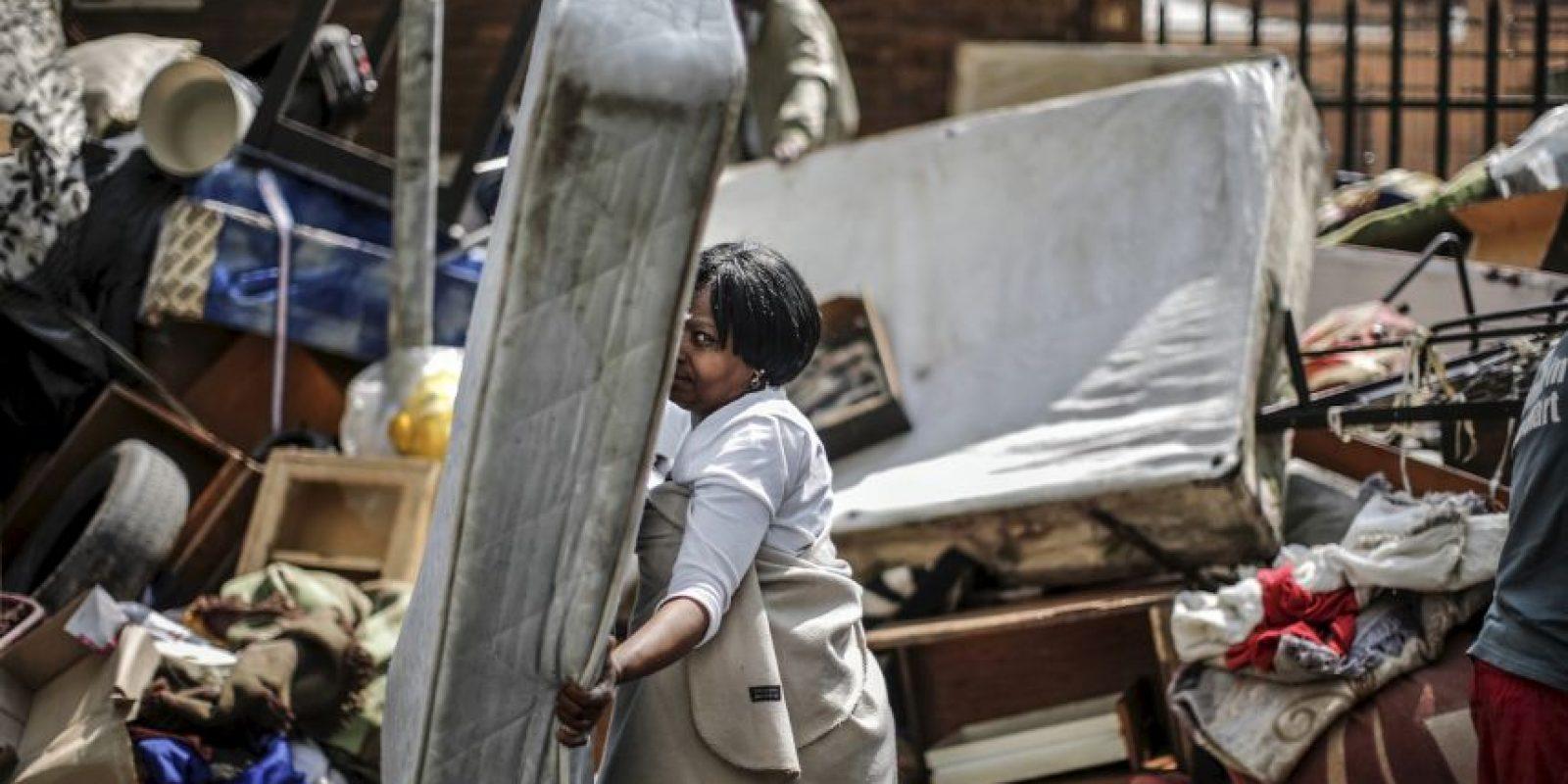 Mujer salva un colchón en Sudáfrica tras quedar una pila de objetos de personas desalojadas. Foto:AFP