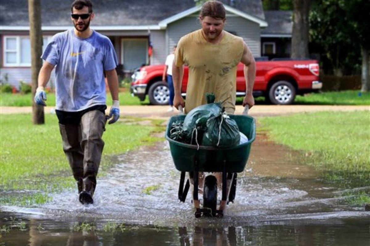 Debido a las inundaciones dos habitantes de Louisiana trasladan sacos de arena en una carretilla en el vecindario de River Oaks, en Lafayette, Louisiana. Foto:AP/ Archivo