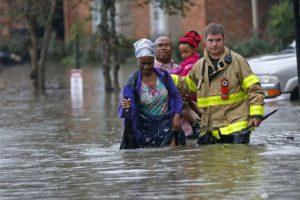 Un integrante del Departamento de Bomberos de St. George ayuda a los habitantes de unos departamentales a caminar entre la inundación. Foto:AP/ Archivo