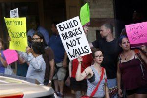 """16 de agosto de 2016. Una mujer sotiene un cartel en el cual se lee """"construye puentes no muros"""", en referencia a las declaraciones de Trump, quien asegura que construira un muro en la frontera de México-EU."""