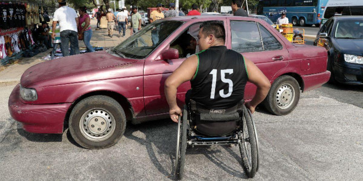 Atletas paralímpicos trabajan en estacionamiento para solventar gastos deportivos