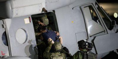 """El capo mexicano del narcotráfico Joaquín """"El Chapo"""" Guzmán es subido a un helicóptero de la Marina en un hangar federal en la Ciudad de México, el viernes 8 de enero de 2016. Foto:AP. Imagen Por:"""