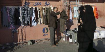 """En esta imagen del jueves 7 de enero de 2016, hombres iraníes cuelgan ropa en un muro benéfico en el centro de Teherán, Irán. Ante la llegada de un invierno brutal, donantes anónimos colocan """"muros de generosidad"""" en todo el país con ganchos invitando a la gente a dejar ropa de abrigo que les sobre o a tomar lo que necesite. Foto:AP. Imagen Por:"""