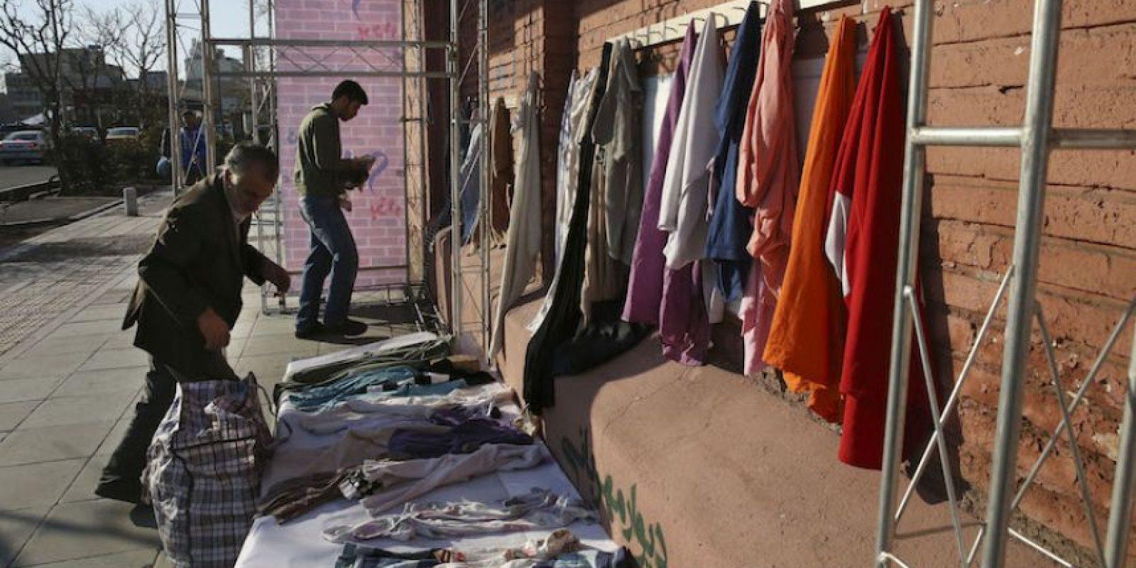 """En esta imagen del jueves 7 de enero de 2016, un hombre iraní cuelga ropa en perchas en un muro benéfico en el centro de Teherán, Irán. Ante la llegada de un invierno brutal, donantes anónimos colocan """"muros de generosidad"""" en todo el país con ganchos invitando a la gente a dejar ropa de abrigo que les sobre o a tomar lo que necesite. Foto:AP. Imagen Por:"""
