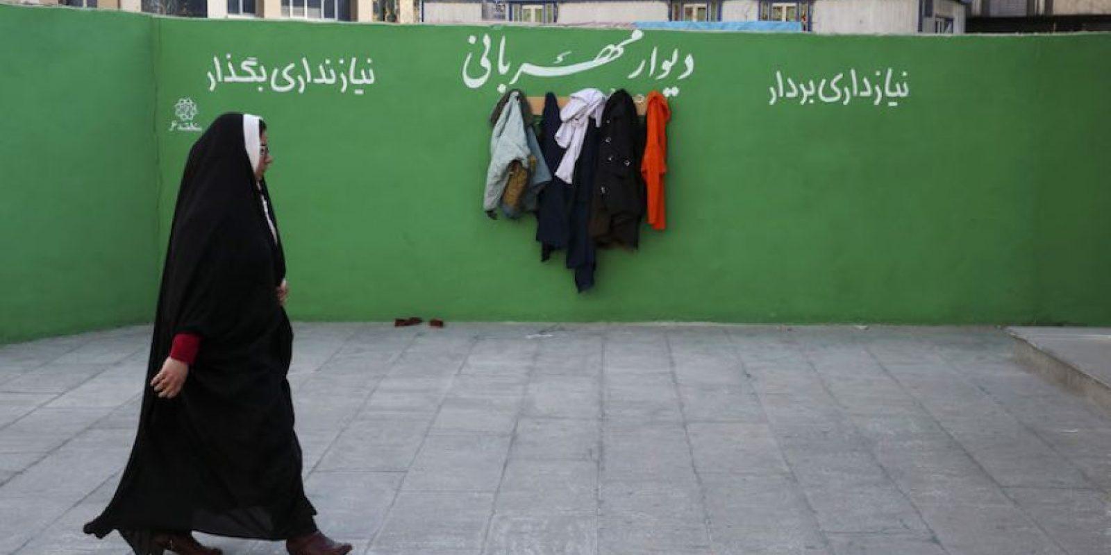 Una mujer iraní pasa junto a un muro con ropa colgada de ganchos en un muro benéfico con el mensaje Foto:AP. Imagen Por: