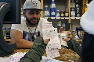 Samir Akhter,propietario de Penn Branch Liquor, intercambia dinero por boletos de la lotería Powerball el sábado 9 de enero de 2016 en Washington. Foto:AP. Imagen Por: