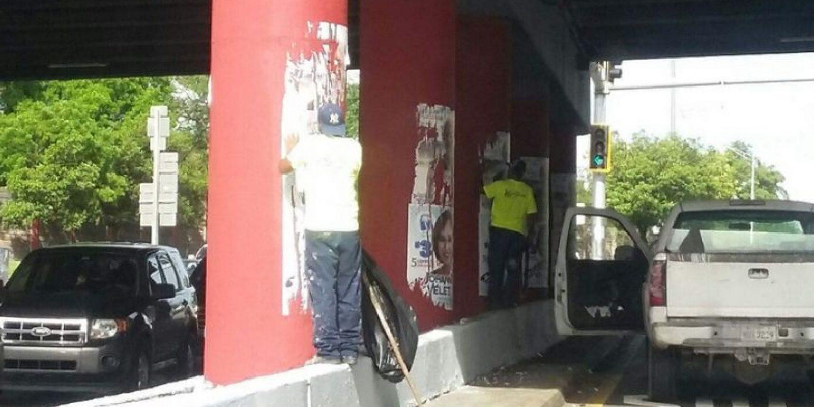Empleado municipal de San Juan remueve propaganda.. Imagen Por: