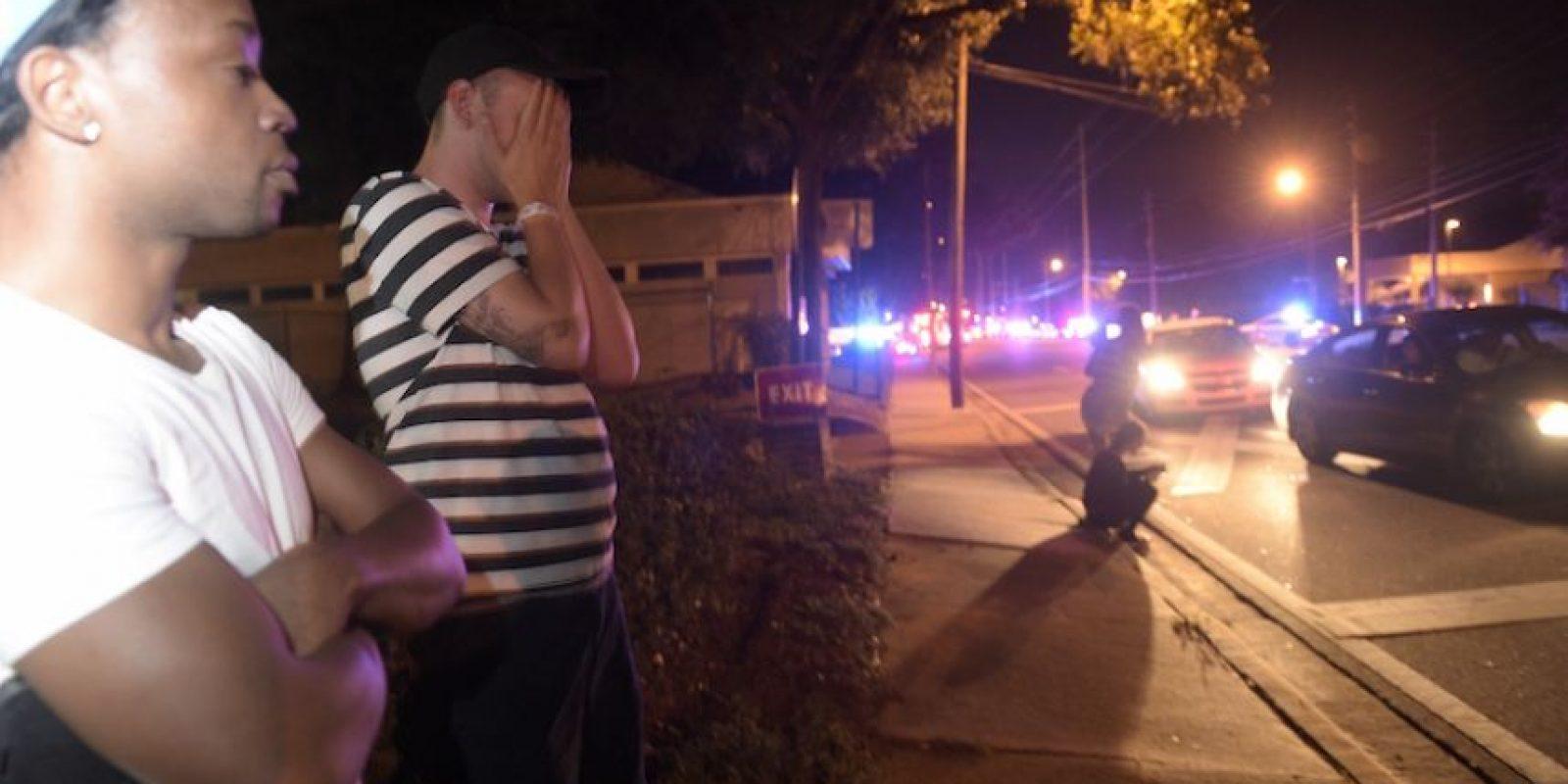 Jermaine Towns (izquierda) y Brandon Shuford observan desde la acera en la misma calle de un club nocturno donde ocurrió una balacera en Orlando, Florida, la madrugada del domingo 12 de junio de 2016. Foto:AP. Imagen Por: