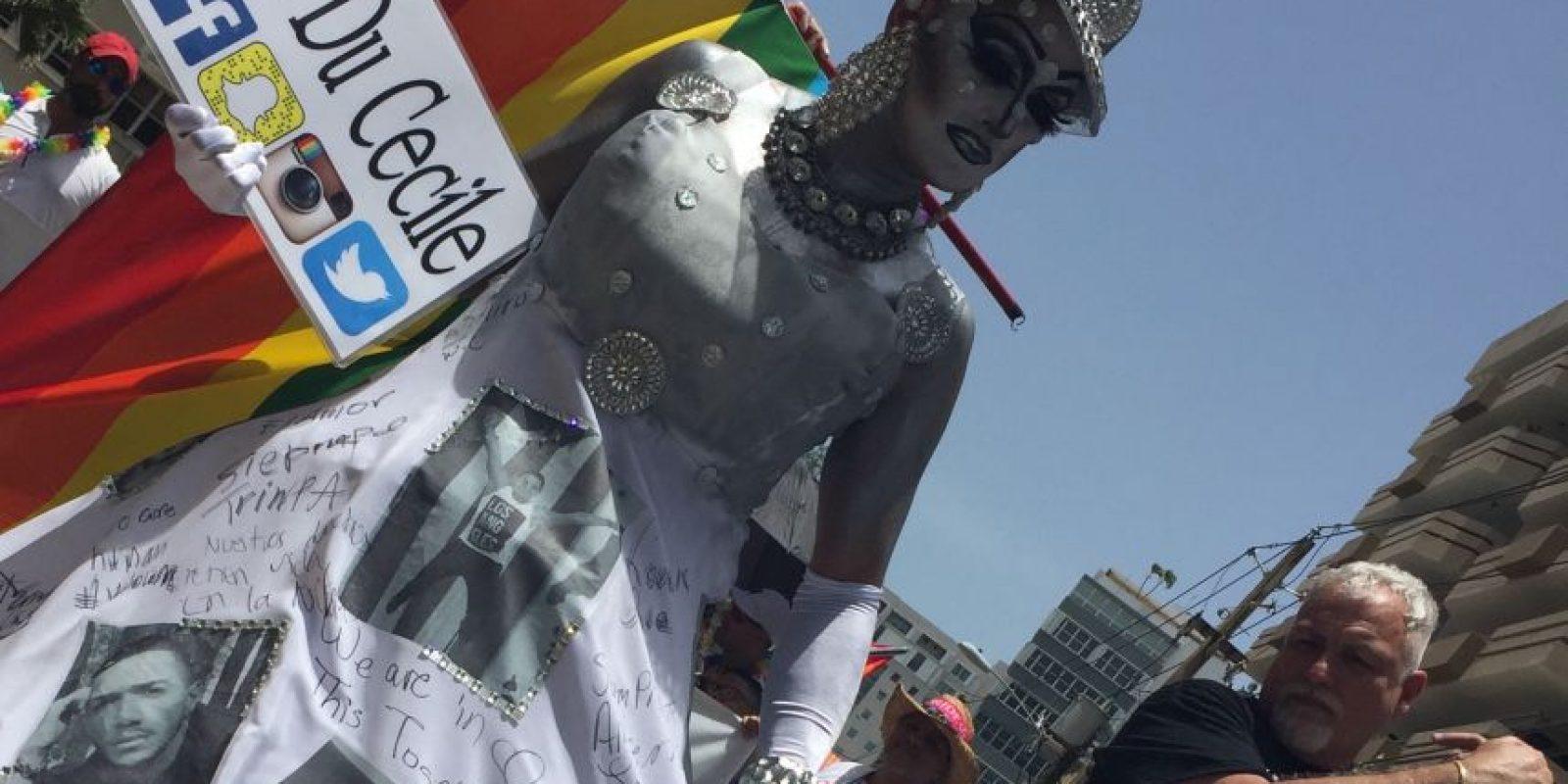 Kriss Du Cecile vistió un traje blanco con tonalidades grises y estampados de las fotos de las 23 víctimas puertorriqueñas, vestuario que además sirvió de tablero para que las personas que así lo quisieran escribieran un mensaje de solidaridad sobre la misma pieza de ropa. Foto:David Cordero Mercado. Imagen Por: