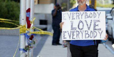 """Chris Bailey camina junto a un altar improvisado en la calle Griffin de Dallas, Texas, con un cartel que dice """"Todos, amen a todos"""", el viernes 8 de julio de 2016. Foto:AP. Imagen Por:"""