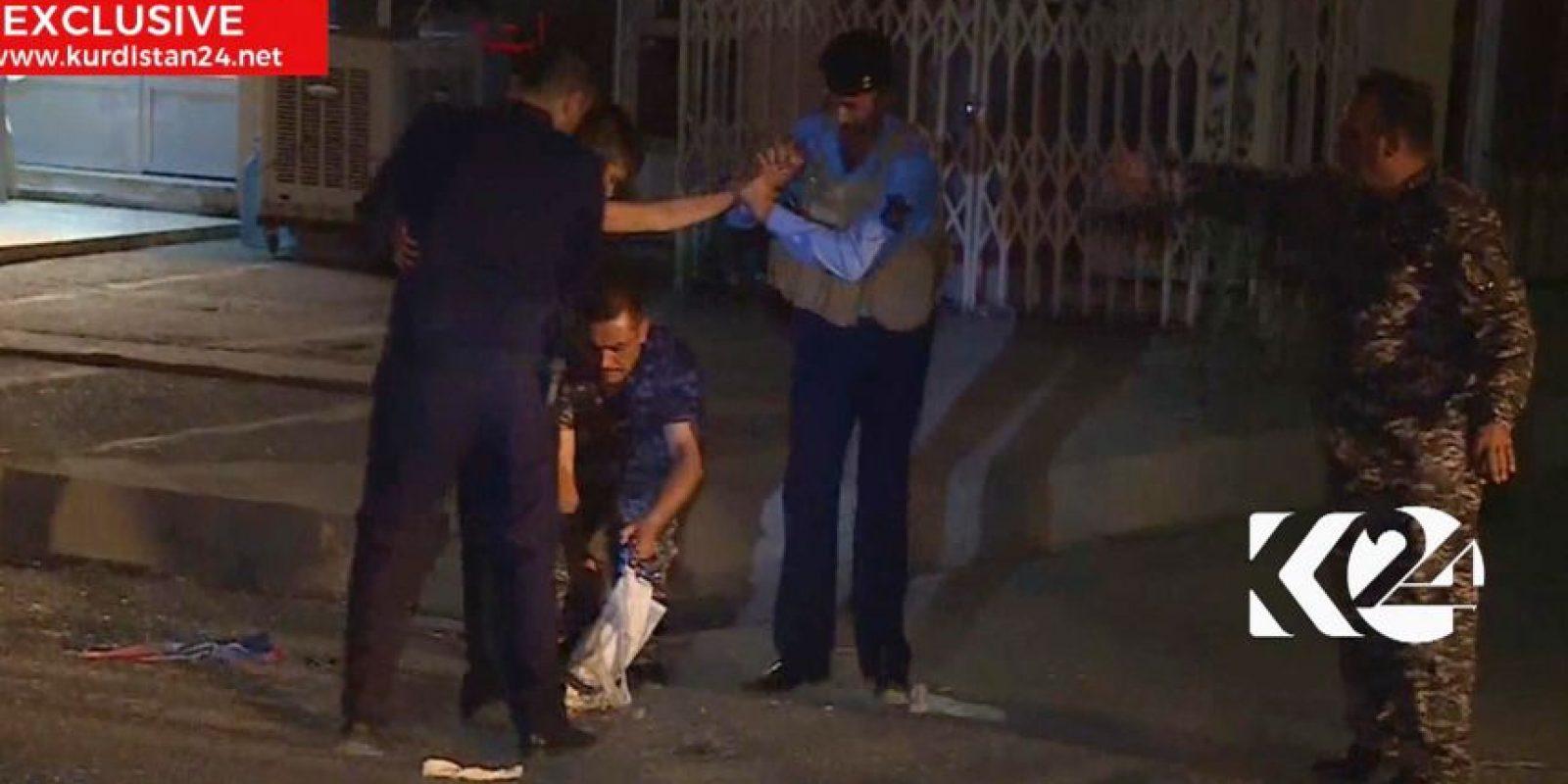 Imagen tomada de la señal de una televisota local que muestra a un niño siendo detenido por agentes de seguridad, uno de los cuales corta un cinturón con explosivos, en Kirkuk, Irak. Foto:AP. Imagen Por: