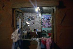 Una niña mira a su espalda mientras hace sus tareas en la barriada Villa 31 de Buenos Aires, Argentina. / AP. Imagen Por: