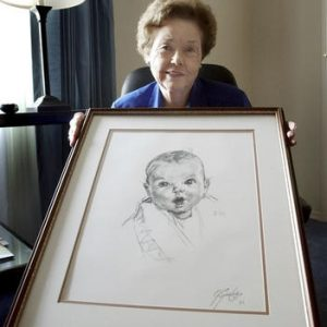FILE - In this Feb. 4, 2004, file photo, Ann Taylor Cook, poses at her Tampa, Fla., home with a copy of her photo that is used on all Gerber baby food products. Gerber says Cook turned 90 on Sunday, Nov. 20, 2016. (AP Photo/Chris O