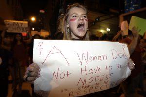"""© Copyright 2017 The Associated Press. All rights reserved.. Imagen Por: Clarissa Horsfall se expresa y lleva una pancarta que dice que """"una mujer no tiene que ser modesta para que sea respetada"""", durante una marcha ayer como parte de la campaña A Day Without a Woman, en Miami, Florida. / Foto: AP"""