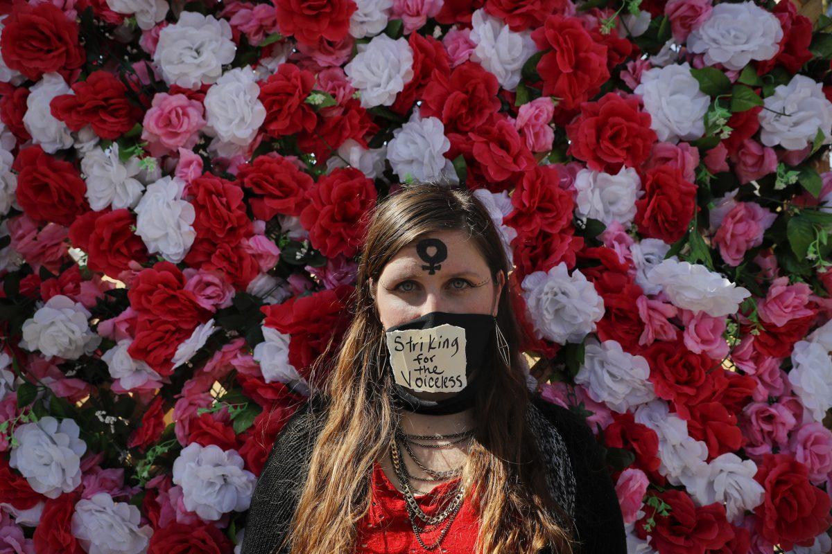 © Copyright 2017 The Associated Press. All rights reserved.. Imagen Por: Hillary Harper, de pie frente a una pared decorada con flores artificiales durante una protesta como parte de la campaña A Day Without a Woman en Los Ángeles, California. Muchas mujeres estadounidenses se quedaron en la casa y no llegaron al trabajo, se unieron a las manifestaciones o usaron vestimenta color rojo para demostrar lo vital que son las mujeres para la economía de Estados Unidos. / Foto: AP