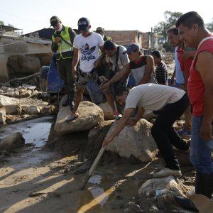 Un grupo de hombres busca un cuerpo entre los escombros y el lodo. Las autoridades colombianas informaron que al menos 273 personas murieron cuando los ríos que rodean a Mocoa se desbordaron y enviaron un muro de agua y escombros a través de la localidad la madrugada del sábado. El número de muertos podría aumentar. (Foto AP / Fernando Vergara)